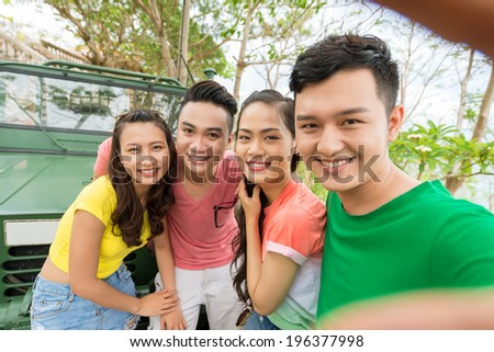 Man taking photo of himself and his friends - stock photo