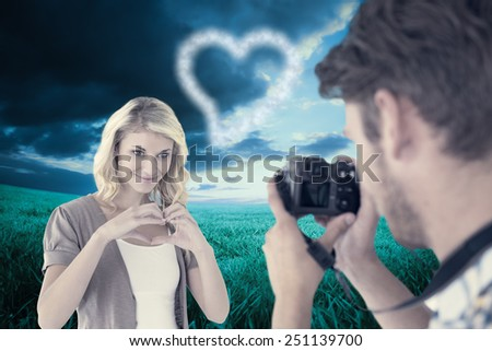 Man taking photo of his pretty girlfriend against blue sky over green field - stock photo