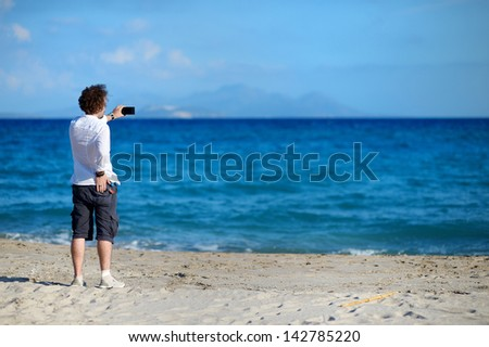 Man taking photo with mobile phone on the beach - stock photo