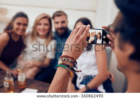 Man taking photograph of his friends with mobile phone. Young people sitting together enjoying at a party. - stock photo
