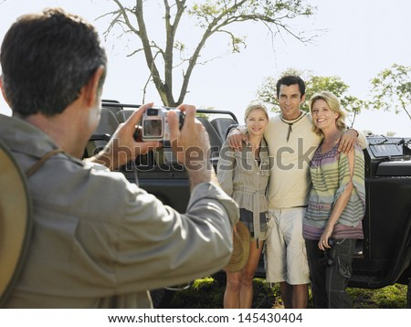 Man taking photograph of three friends against jeep - stock photo