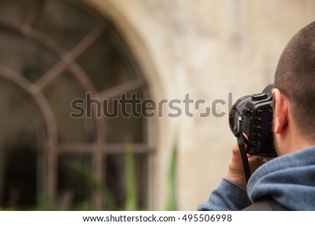 Man taking photos of old building with big windiw