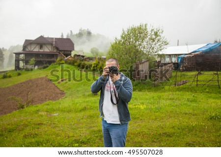 Man taking photos on the meadow in the countryside
