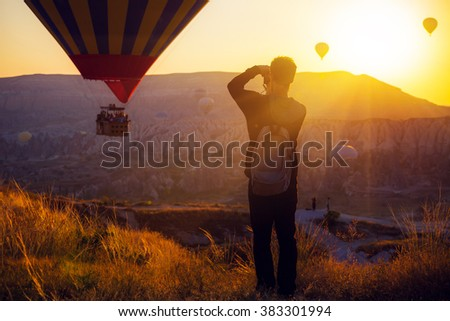 man taking picture of Hot air balloons flying over spectacular Cappadocia - stock photo