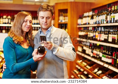 Man taking picture of wine bottle in supermarket with his smartphone - stock photo