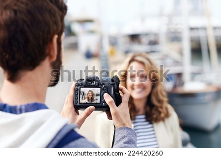 Man taking pictures of girlfriend on holiday travel vacation tourist couple - stock photo
