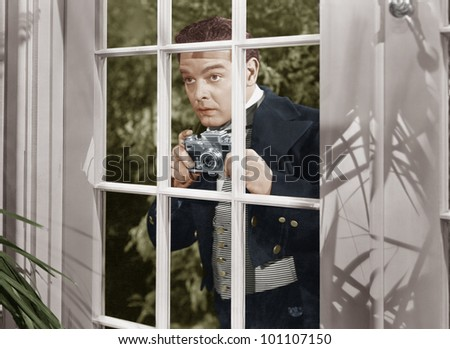 Man taking pictures through window - stock photo