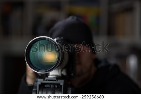 Man taking pictures with large telephoto lens - stock photo