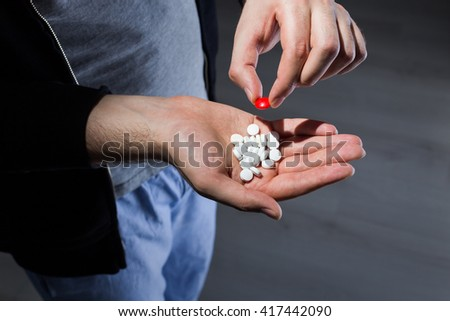 Man taking red pill from white pill pile in hand