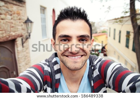 Man taking self portrait in the europe streets.Athens,Greece.Smiling young man.Travel selfie. - stock photo
