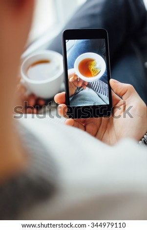 Man taking self portrait with cup of tea - stock photo