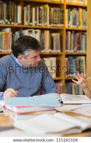 Man talking in library while reading a book
