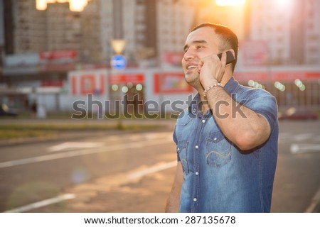 Man talking on a cell phone. Male and mobile phone. Man of Asian appearance is in the rays of a sunset on the background of urban buildings. Concept of a person's life in a big modern city. Azerbaijan - stock photo