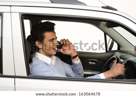 Man talking on a mobile phone while driving a car