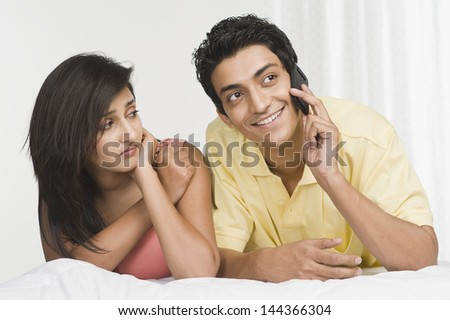 Man talking on a mobile phone with a woman looking sad beside him