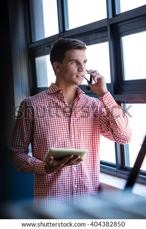 Man talking on mobile phone and holding digital tablet in office - stock photo
