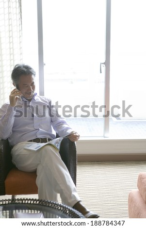 man talking on mobile phone while reading book