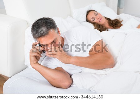 Man Talking On Phone While Woman Sleeping On Bed - stock photo