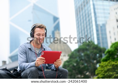 Man talking on tablet pc having video chat conversation in sitting outside using app on 4g wireless device wearing headphones. Casual young urban professional male in his late 20s. Hong Kong.