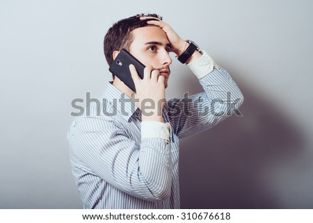 man talking on the phone and holding his head - stock photo