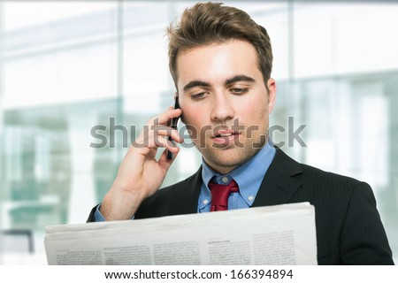 Man talking on the phone while reading the newspaper - stock photo