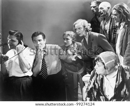 Man talking on the telephone and his friends looking at him and trying to listen - stock photo