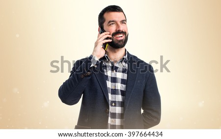 Man talking to mobile over ocher background
