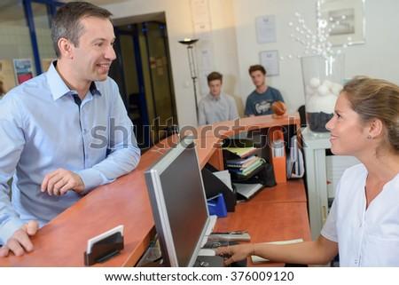 Man talking to receptionist - stock photo