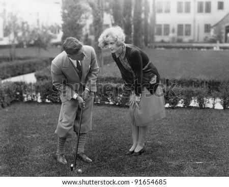 Man talking to woman while golfing - stock photo