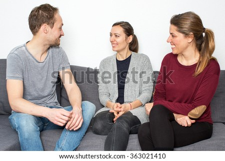 Man talking with two women - stock photo