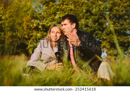 Man talks to a girl sitting on a meadow in the park - stock photo