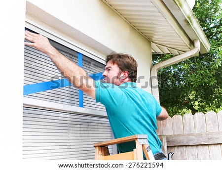 Man taping the windows on his home to protect from broken glass in a hurricane.   - stock photo