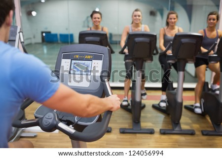 Man teaches spinning class to happy women at gym - stock photo