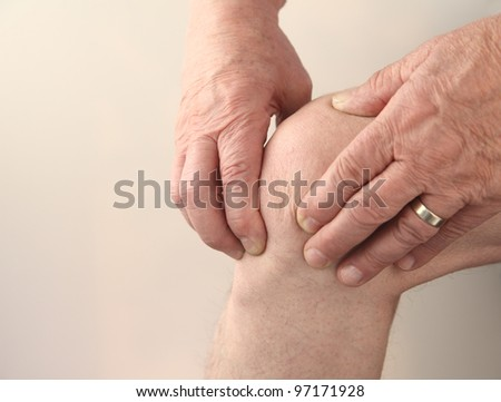 man tends to his sore knee - stock photo