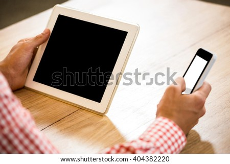 Man text messaging on mobile phone and holding digital tablet in office - stock photo
