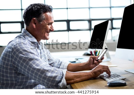 Man text messaging on mobile phone while using computer in office - stock photo