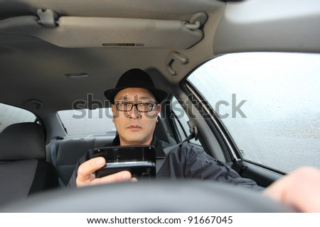 Man texting on cellphone while driving on a rainy day.