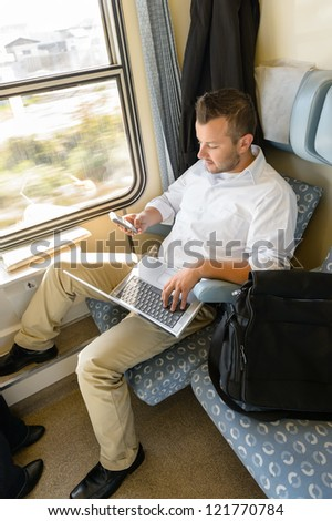 Man texting on phone holding laptop train commuter work journey - stock photo