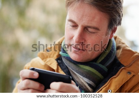Man Texting On Smartphone Wearing Winter Clothes - stock photo