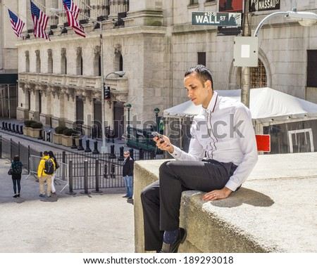 Man Texting on Wall Street.  Wearing a white shirt, black pants, under sunshine,  a young handsome guy is sitting outside office building, texting on his cell phone. Wall Street sign in background.  - stock photo