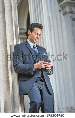 Man Texting Outside. Dressing in dark blue suit, necktie, a handsome, sexy, middle age businessman is standing outside office, looking down, texting on cell phone.  - stock photo