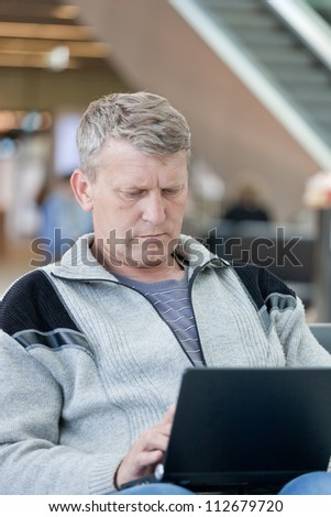 man the passenger with the laptop in a waiting room of the modern station