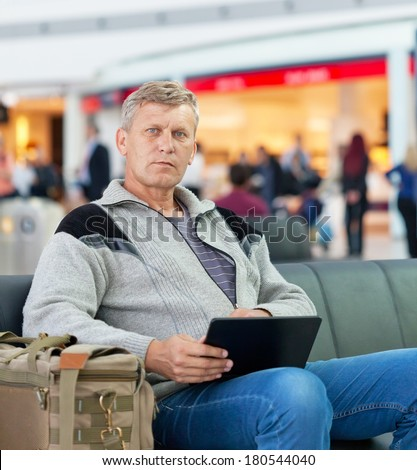 man the passenger with the laptop in a waiting room of the modern station - stock photo