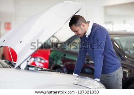 Man thinking about a car engine in a garage