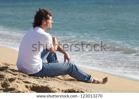 Man thinking and watching the sea on the beach - stock photo