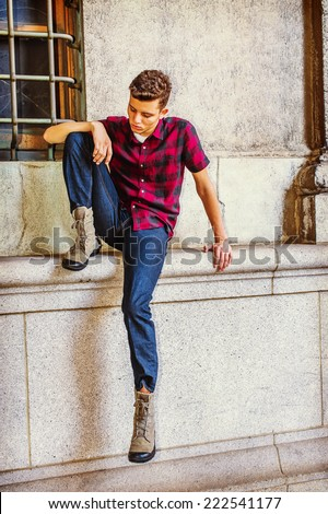 Man Thinking Outside. Dressing in a short sleeve, black, red patterned shirt, jeans, boot shoes, a young handsome guy is sitting by a window, lowering head, looking down at his foot, sad, thinking