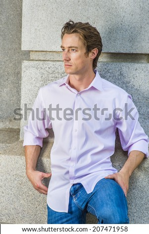 Man Thinking Outside. Wearing a light pink, long sleeve shirt, blue jeans, bending a leg, a young handsome guy is standing against a concrete wall, looking around, thinking - stock photo