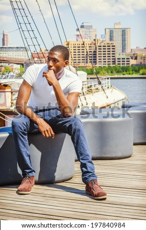 Man Thinking Outside. Wearing a white T shirt, blue pants, brown boot shoes, a young black guy is sitting on deck, a hand touching his mouth, relaxing, lost in thought. The background is a harbor. - stock photo
