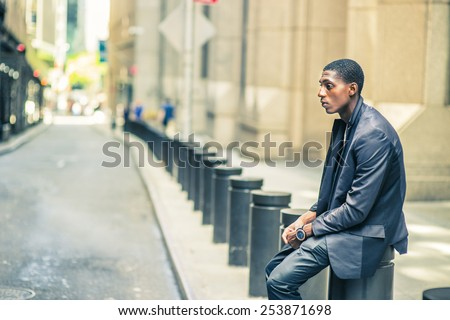 Man thinking outside. Young black teenage boy is sitting on street, hunchbacked, sad, tired, looking down, thinking, lost in thought. Retro filtered look.  - stock photo