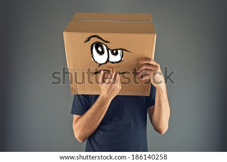 Man thinking with cardboard box on his head with serious emoticon face expression. - stock photo